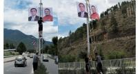 Workers install posters of Prime Minister of Bhutan Tshering Tobgay, right, and Prime Minister General Prayut Chan-o-cha and the countries' national flags along an expressway in the capital city Thimphu, Bhutan.