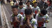 Twelve boys and their football coach Ekkapol Chantawong (C), dramatically rescued from deep inside a Thai cave after being trapped for more than a fortnight, arrives for a press conference in Chiang Rai on Wednesday. // AFP PHOTO