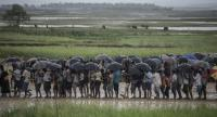 (FILES) In this file photo taken on October 06, 2017, Rohingya Muslim refugees wait in line under the rain during a food distribution under at Nayapara refugee camp in Bangladesh's Ukhia district. PHOTO: AFP