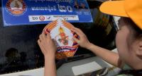 A volunteer of ruling Cambodian People's Party (CPP) place a party sticker on a vehicle during a campaign in Phnom Penh ahead of the July 29 general election. /AFP