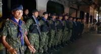 A joint security team of volunteer police, military, and Volunteer Defence Corps get ready for night duty.