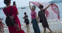Mainland Chinese tourists pose for photographs on a beach at Repulse Bay in Hong Kong, China on July 16.//EPA-EFE