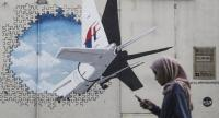 A woman walks in front of a Malaysia Airlines flight MH370 mural painting at Shah Alam, outside Kuala Lumpur, Malaysia on July 29.//EPA-EFE