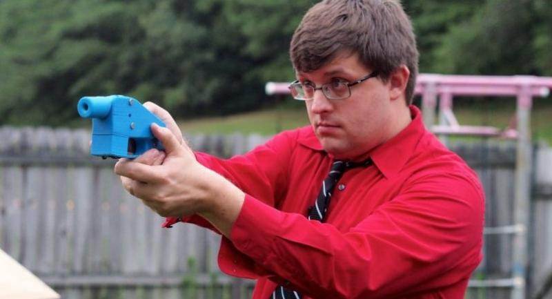 In this file photo taken on July 11, 2013, software engineer Travis Lerol takes aim with an unloaded Liberator handgun in the backyard of his home./AFP