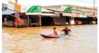 Residents paddle through rising water around flooded market stalls in Stung Treng province's Stung Treng town in 2013. Photo supplied