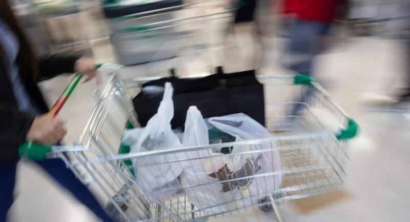 A customer uses plastic bags at a supermarket. // AFP PHOTO