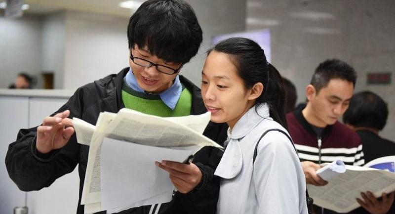 Job-seekers read post information at a job fair for young people across the Taiwan Strait at Suzhou, Jiangsu province, Dec 11, 2016. [Photo/VCG]
