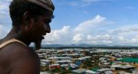 A Rohingya refugee looks on as the Kutupalong camp is seen on the background in Ukhia on August 8, 2018. (Photo by CHANDAN KHANNA / AFP)