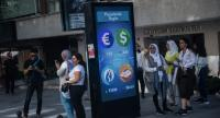 People stand next to a digital billboard giving updates on various currencies and the Turkish stock exchange in Istanbul on August 13, 2018. - Turkey's troubled lira tumbled on August 13 to fresh record lows against the euro and dollar.--Photo by AFP