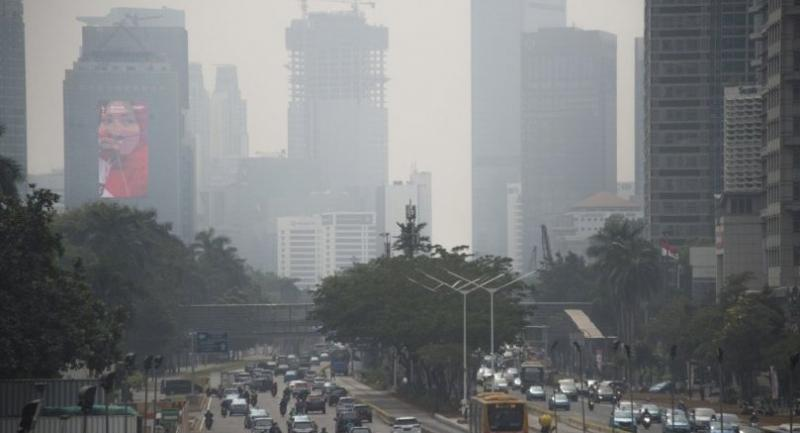 This photograph taken on August 8, 2018 shows a 2018 Asian Games promotional billboard on a building (L) as seen past traffic and haze from air pollution in Jakarta's city centre./AFP