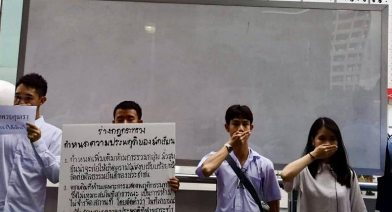Student activists symbolically cover their mouths in protest against regulations they believe are aimed at quelling political expression.
