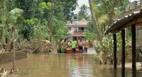 Kerala and Tamil Nadu Fire Force personnel transport children and elderly people in a dinghy through flood waters during a rescue operation in Annamanada village in Thrissur District, in the south Indian state of Kerala, on August 19, 2018. // AFP