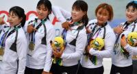 Members of the Unified Korea team pose on the podium after receiving their bronze medals during a medal ceremony for the women's canoe 200m traditional boat race at the 2018 Asian Games in Palembang on August 25, 2018. (Photo by ADEK BERRY / AFP)