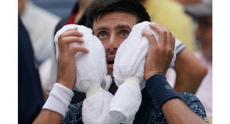 Novak Djokovic of Serbia towels off in the heat against Marton Fucsovics of Hungary.