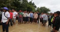 Win Myat Aye, Union Minister for Social Welfare, Relief and Resettlement (on phone in beige traditional coat) inspects flood damage in Yedashe township. (Photo courtesy of the ministry)