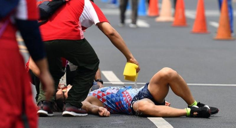South Korean Joo Hyun-myeong gets water from medic after he finishing the men's 50km walk race competition during the 2018 Asian Games in Jakarta on August 30, 2018. (Photo by Juni Kriswanto / AFP)