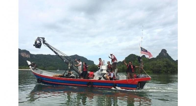 Lights, camera, action: Part of the local filming crew for 'Crazy Rich Asians' shooting the private island scene on a boat in Langkawi, Kedah. — Photo courtesy of Biscuit Films