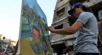 An artist paints in the the Yarmuk Palestinian refugee camp on the southern outskirts of the capital Damascus./AFP