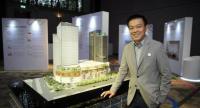 Thanapol Sirithanachai, president of Golden Land Property Development Plc, poses with the model of Samyan Mitrtown.