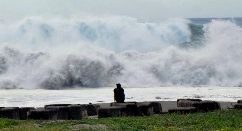 This CNA handout picture taken and released on September 14, 2018 shows a man watching huge waves crashing into the coast at Taitung county, eastern Taiwan, as Super Typhoon Mangkhut approaches the southern sea of Taiwan. // AFP PHOTO