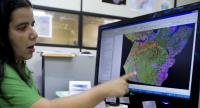 In this file photo taken on November 27, 2009 Priscila Santos, a Brazilian Environmental Intitute geographer points at a satellite map to detect deforestation areas in the Para state in Santarem , northern Brazil./AFP