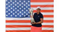 US golfer Angela Stanford poses with her trophy in front of the US national flag after winning the Evian Championship.