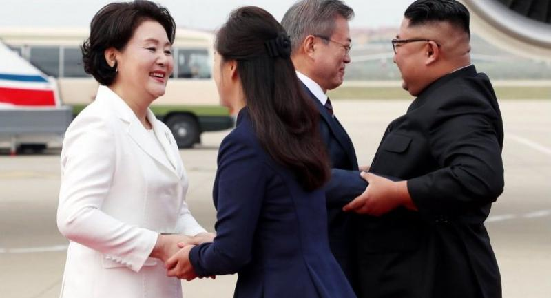 North Korean leader Kim Jong Un (R) and his wife Ri Sol Ju (2nd L) welcome South Korean President Moon Jae-in (2nd R) and his wife Kim Jung-sook (L) during a welcoming ceremony at Pyongyang SooAn airport on September 18, 2018./AFP