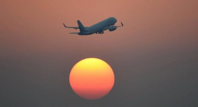 This file photo taken on February 10, 2016 shows an aircraft of India's IndiGo in flight as the sun set in New Delhi.//AFP