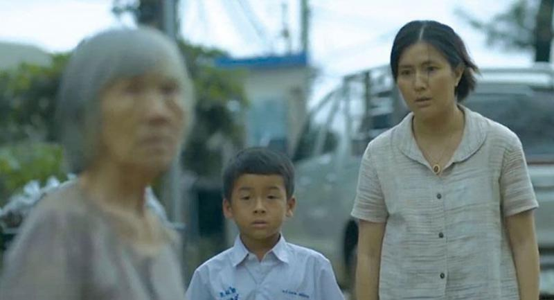 "This still from the short film, ""Katanyoo"" (Gratitude), shows a boy approaching an old lady standing alone on the street to offer her help. The film is about a teacher who takes care of his Alzheimer's afflicted mother."