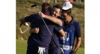 Europe's Northern Irish golfer Rory McIlroy (R) celebrates with Europe's English golfer Ian Poulter after winning their foursomes match on the first day .