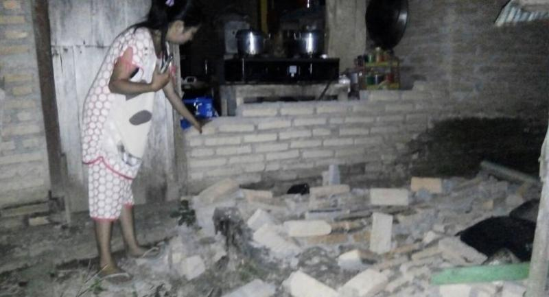 A resident is seen beside the collapsed brick wall of her house at Tobadak village in Central Mamuju, western Sulawesi province, on September 28, 2018, after a strong earthquake hit the area./AFP