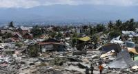 Residents walk amid debris in Perumnas Balaroa village in Palu, Indonesia's Central Sulawesi on October 2, 2018, after an earthquake and tsunami hit the area on September 28./AFP