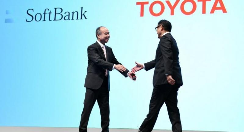 SoftBank Group head Masayoshi Son (L) welcomes Toyota Motor president Akio Toyoda (R) during their joint press conference in Tokyo on October 4, 2018./AFP