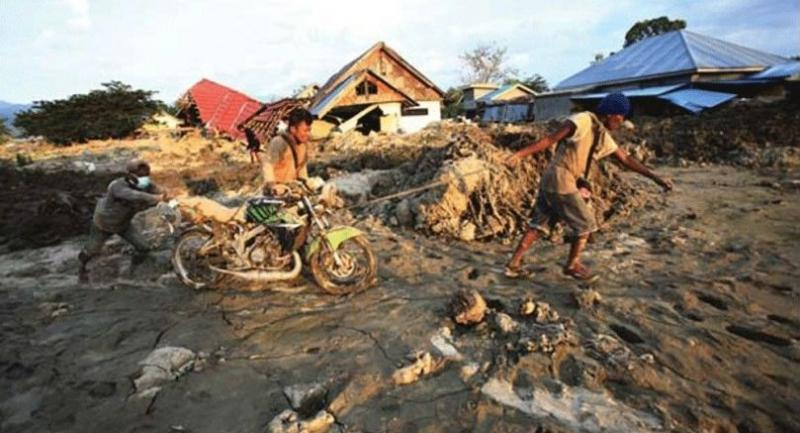 Muddy ruins: People drag a motorcycle out of the mud on Wednesday in the Petobo area of Palu, Central Sulawesi.  (The Jakarta Post/Dhoni Setiawan)