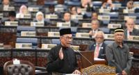Malaysia's People's Justice Party president and leader of the Pakatan Harapan coalition Anwar Ibrahim (C) takes an oath as a member of the parliament during swearing in ceremony at Parliament House in Kuala Lumpur on October 15.//AFP