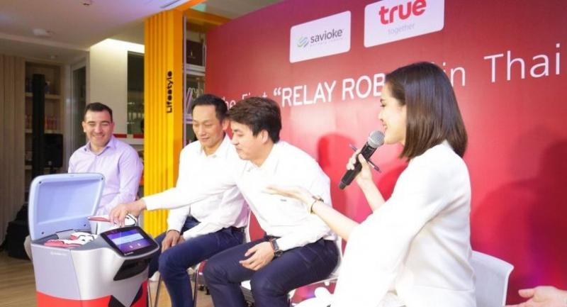 Songtham Phianattanawit, second from left, managing director of IoT business at True Corporation, is with executives showing off the Relay robot during a presentation on the device's capabilities for delivery services.
