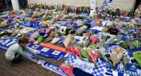 A boy arranges a club scarf around floral tributes piled outside Leicester City Football Club's King Power Stadium in Leicester, eastern England, on October 28, 2018. // AFP PHOTO