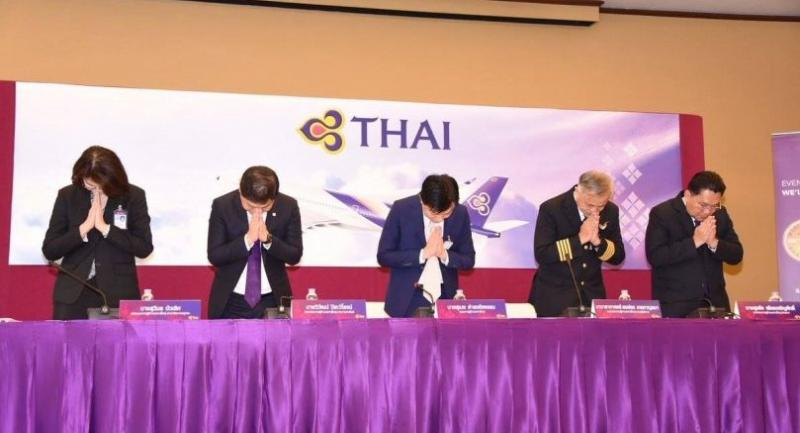Thai Airways International executives bow in apology over a flight delay stemming from two off-duty pilots' insistence on being given first-class seats. In the middle is THAI president Sumeth Damrongchaitham.