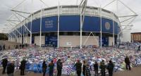 People pause to view and pay their respects at the tributes layed outside Leicester City Football Club's King Power Stadium in Leicester, eastern England, on November 1, 2018 ./AFP