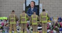 Firefighters pay their respects in front of a portrait of Leicester City Football Club's Thai chairman Vichai Srivaddhanaprabha among the tributes layed outside the club's King Power Stadium in Leicester, eastern England, on November 1./AFP