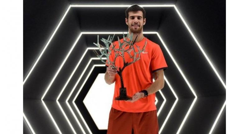Russia's Karen Khachanov poses with the trophy after winning against Serbia's Novak Djokovic.