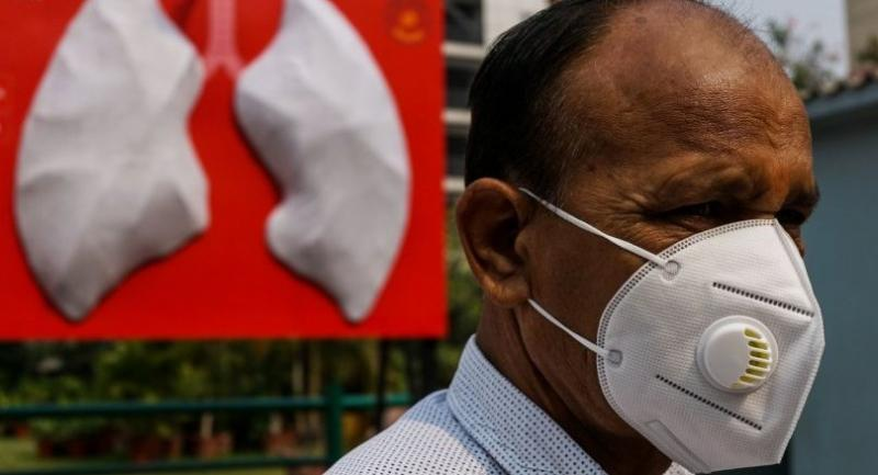 In this photograph taken on November 3, 2018, a man wears a face mask near the installation of a giant set of lungs at Shri Ganga Ram hospital in New Delhi./AFP
