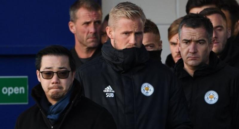 Leicester City's Danish goalkeeper Kasper Schmeichel (C) and Aiyawatt Srivaddhanaprabha (L) the son of Leicester City's late Thai chairman Vichai look at the floral tributes left to victims of the crash at Leicester City Football Club.//AFP