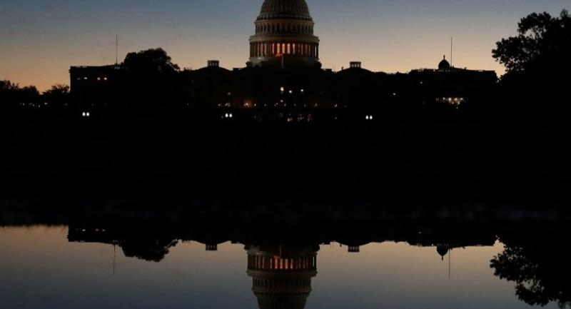 The U.S. Capitol is reflected in a puddle of water a day after Americans voted in the midterm elections, on November 7, in Washington, DC//AFP