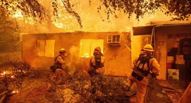 Firefighters push down a wall while battling against a burning apartment complex in Paradise, north of Sacramento, California on November 09.//AFP