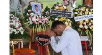 A mourner prays in front of a portrait of 13-year-old Muay Thai boxer Anucha Tasako next to his coffin during a funeral at a Buddhist temple in Samut Prakan province on November 14, 2018.