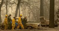 Rescue workers carry a body away from a burned property in the Holly Hills area of Paradise, California on November 14, 2018./AFP