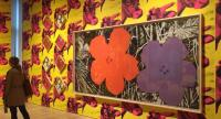 "A woman looks at paintings from the ""Flower"" series against a backdrop of ""Cow Wallpaper"" (1966) by late US artist Andy Warhol at the exhibition 0"" at the Whitney Museum in New York."