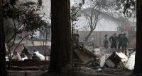 Sheriff deputies and rescue workers recover human remains from a home destroyed by the Camp Fire on November 16, 2018 in Paradise, California./AFP