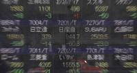 A picture taken in Tokyo on November 20, 2018 shows the stock indicator of Nissan (middle) on an electronic board at the window of a securities company./AFP